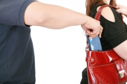 Man Pickpocketing A Purse From Womans Bag